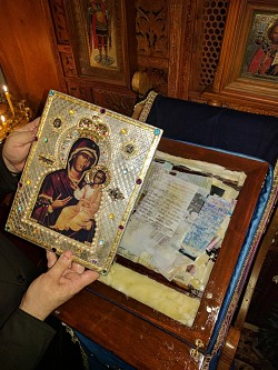 The Holy Icon rests on a bed of cotton, photos and commemoration prayer slips.